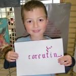 Enfant montrant son prénom en calligraphie